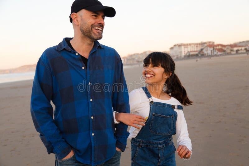 Отец и дочь смеясь пока идущ на пляж стоковое изображение rf