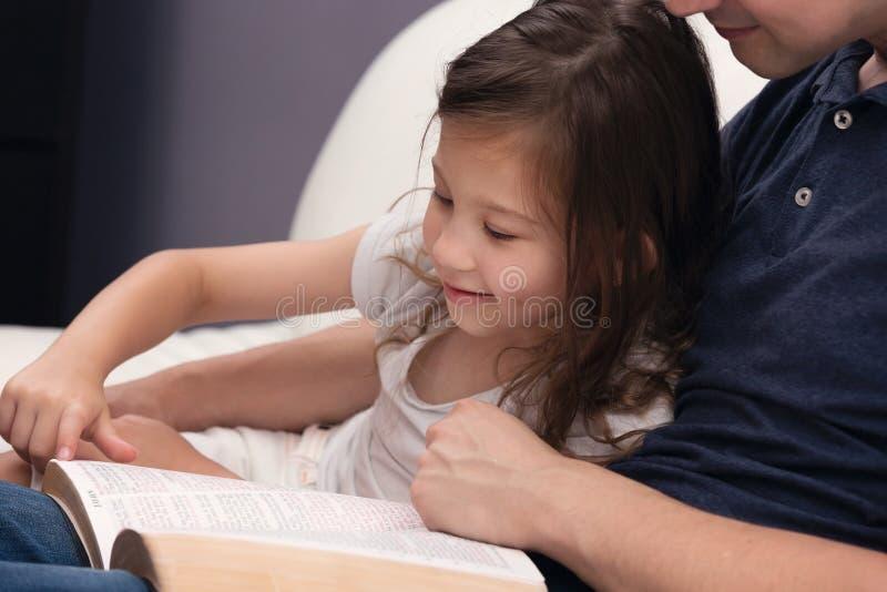 Отец и дочь читая библию стоковые фотографии rf