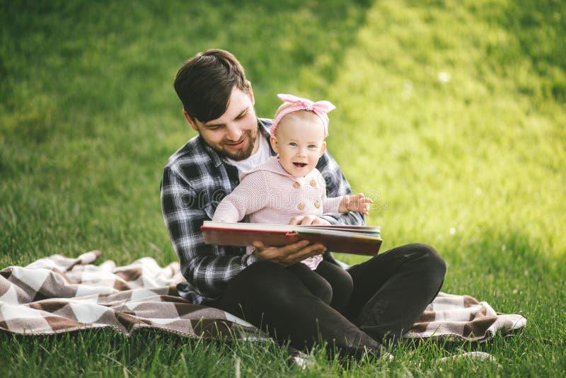 Отец и его маленькая книга чтения daugter младенца в парке стоковые фото