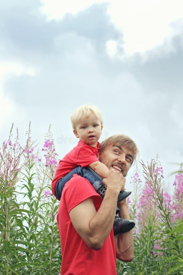 Отец и его маленький сын имеют потеху на зацветая поле fireweed C стоковая фотография rf