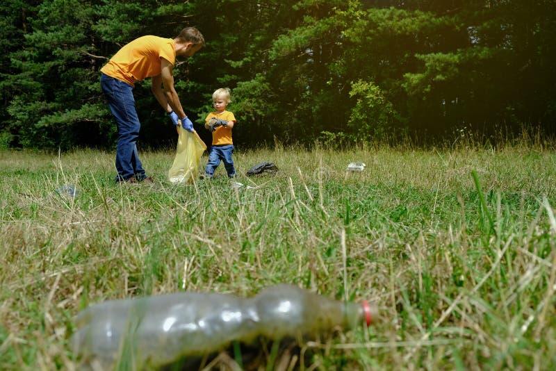 Отец и его маленький сын собирая отброс и пластиковые бутылки в парке Семья волонтеров комплектуя вверх сор в лесе стоковые фотографии rf