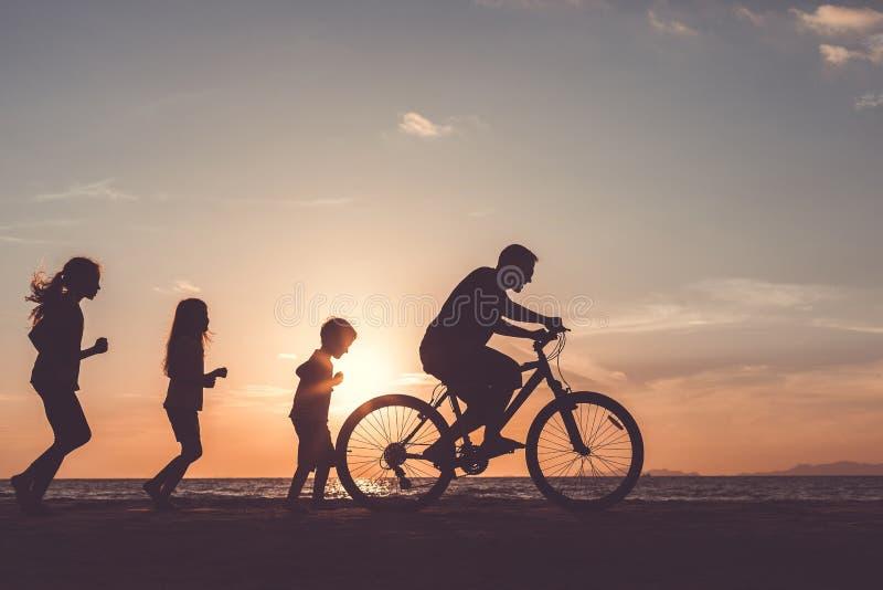 Отец и дети играя на пляже на времени захода солнца стоковое изображение