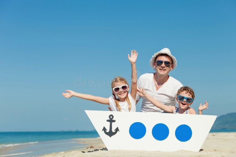 Отец и дети играя на пляже на времени дня стоковая фотография