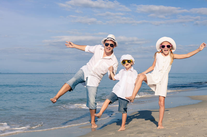 Отец и дети играя на пляже на времени дня стоковые изображения