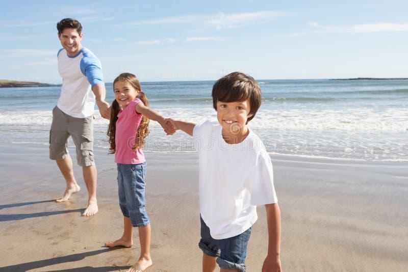 Отец и дети имея потеху на празднике пляжа стоковая фотография