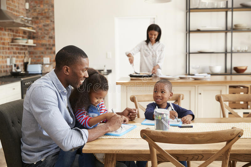 Отец и дети рисуя на таблице как мать подготавливают еду стоковая фотография