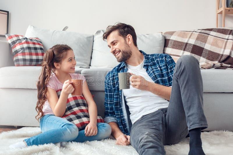 Отец и маленькая дочь дома сидя на поле выпивая горячий шоколад радостный стоковое изображение