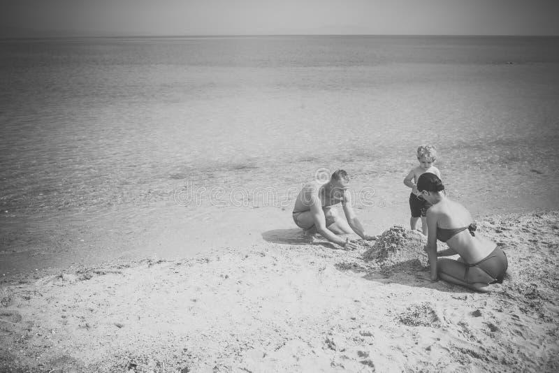 Отец и мать играют с сыном на seashore Семья тратит время совместно и имеющ потеху Милая игра мальчика ребенка с песком стоковое изображение
