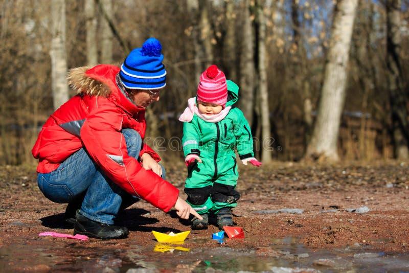 Отец и маленькая дочь играя с водой весной стоковые фотографии rf