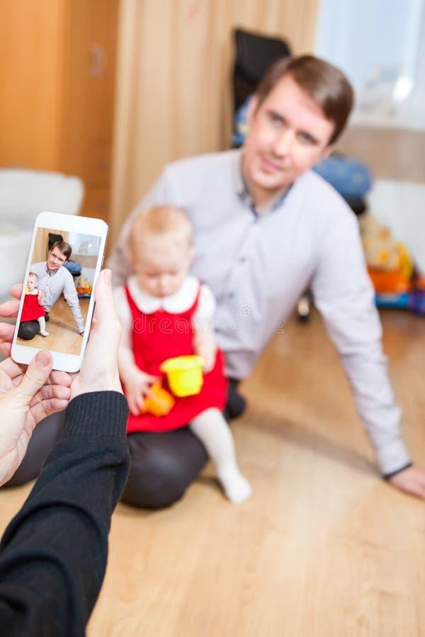 Отец и маленькая дочь представляя мать пока она принимая фото с мобильным телефоном стоковое изображение