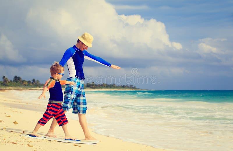 Отец и маленький сын практикуя занимающся серфингом positin стоковое фото rf