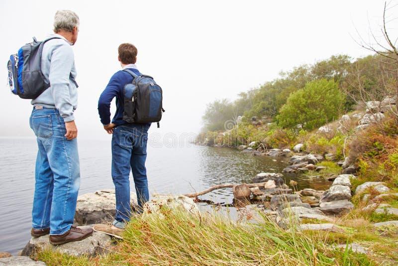 Отец и молодой взрослый сын готовя озеро восхищая взгляд стоковые фотографии rf