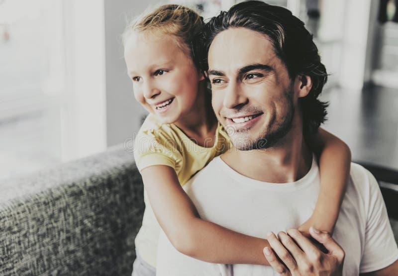 Отец и обнимать и Watcing дочери один другого стоковые изображения