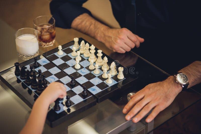Отец и дочь играя шахмат дома стоковая фотография rf