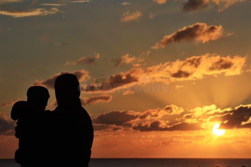 Отец и дочь наслаждаясь заходом солнца стоковое фото rf