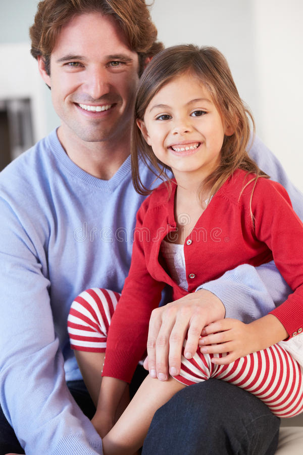 Отец и дочь ослабляя на софе совместно стоковая фотография