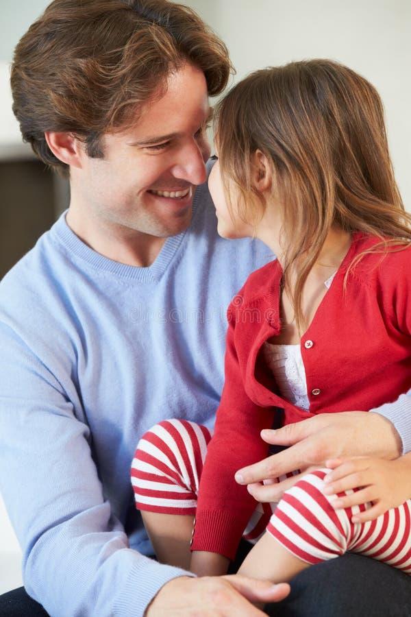 Отец и дочь ослабляя на софе совместно стоковые изображения