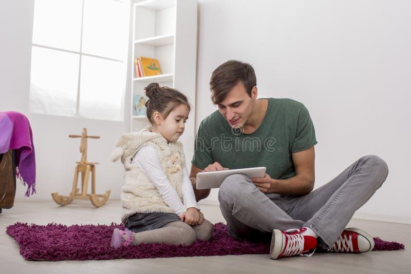 Отец и дочь с таблеткой стоковые изображения rf