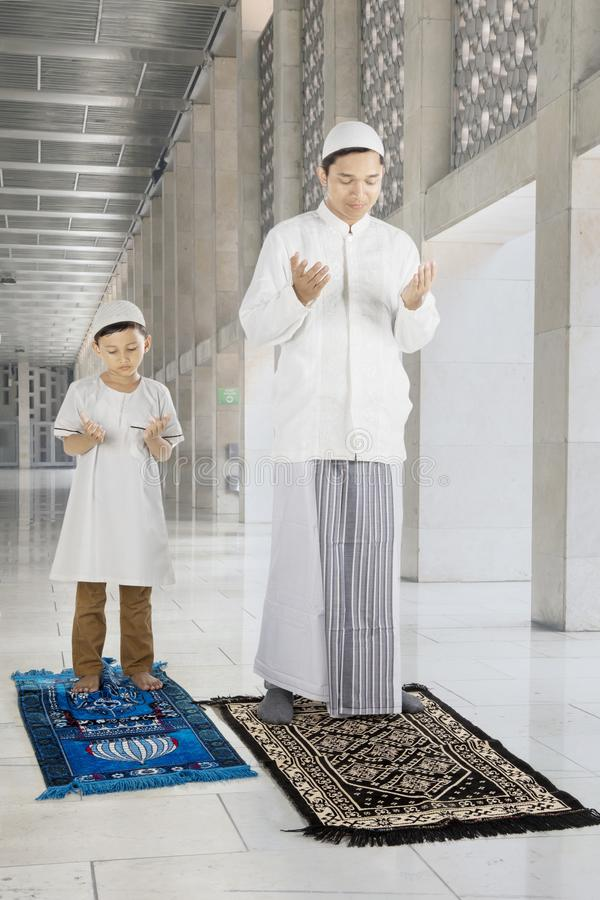 Отец и ребенок молят к БОГУ в мечети стоковые изображения rf