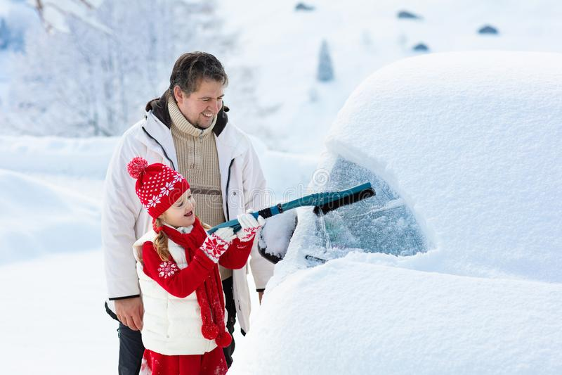 Отец и ребенок чистя автомобиль щеткой в зиме стоковая фотография rf