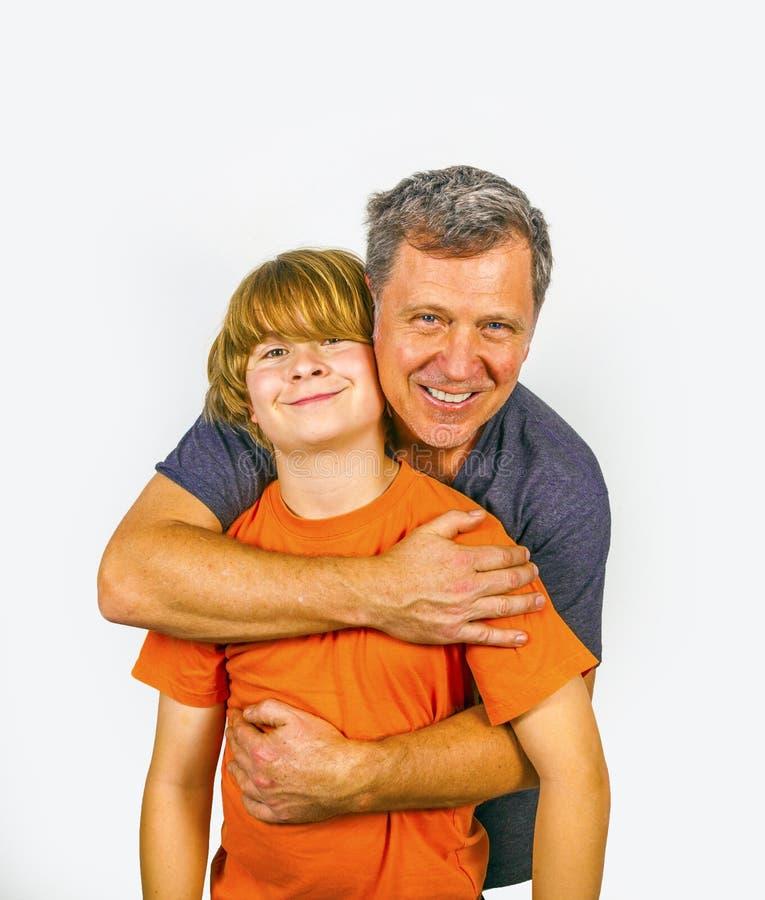 Отец и счастливый обнимать сына стоковое изображение