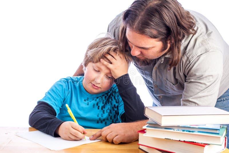 Отец и сынок делая домашнюю работу стоковые фото