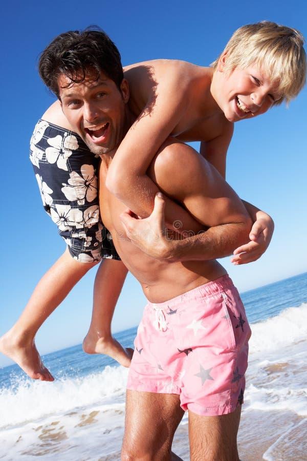 Отец и сынок имея потеху на пляже стоковая фотография rf