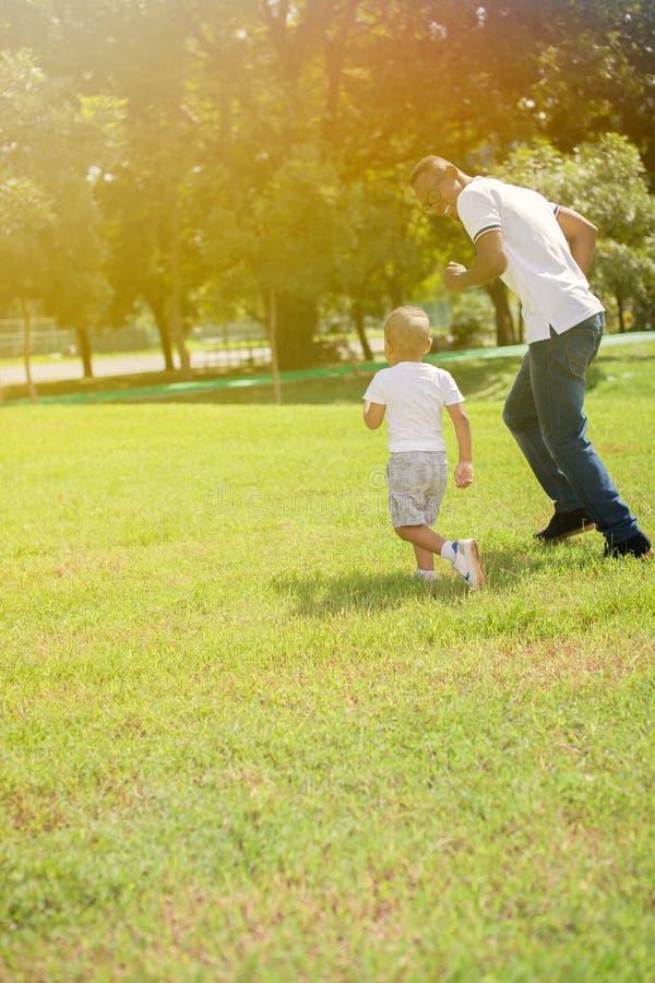 Отец и сын бежать и гоня один другого в зеленом парке стоковая фотография