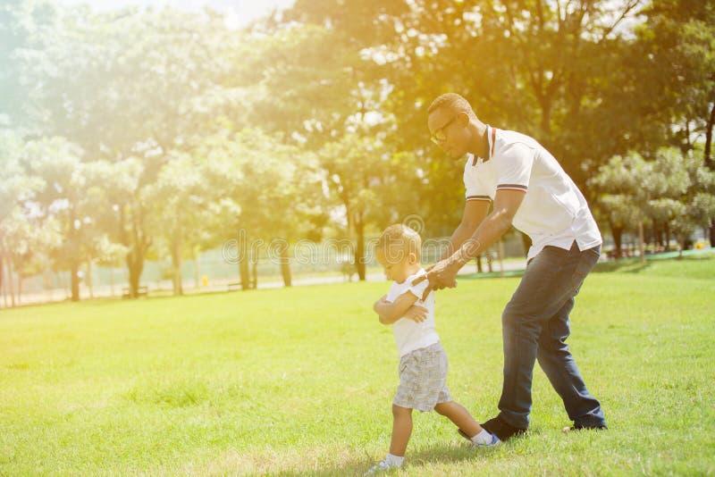 Отец и сын бежать и гоня один другого в зеленом парке стоковое изображение