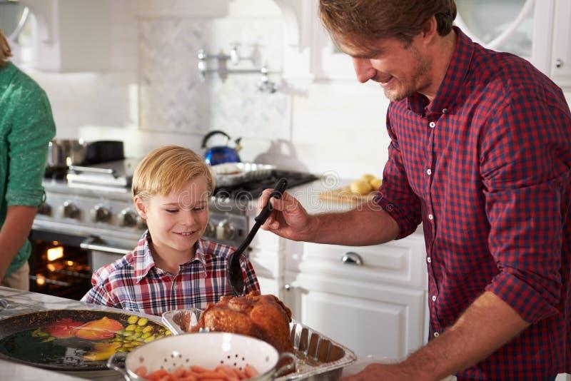 Отец и сын варя жаркое Турцию в кухне совместно стоковая фотография