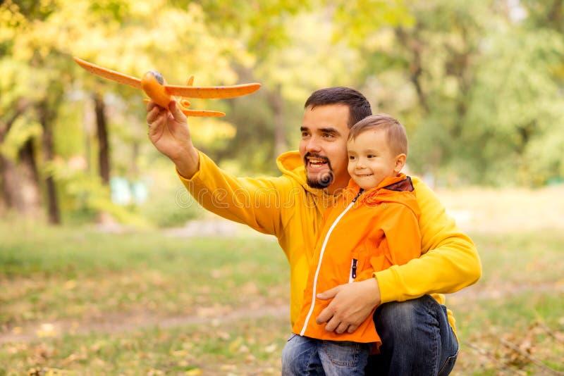 отец и сын веселятся в осеннем парке, запускают игрушечный самолет на улице Желтые деревья на заднем плане стоковое фото rf
