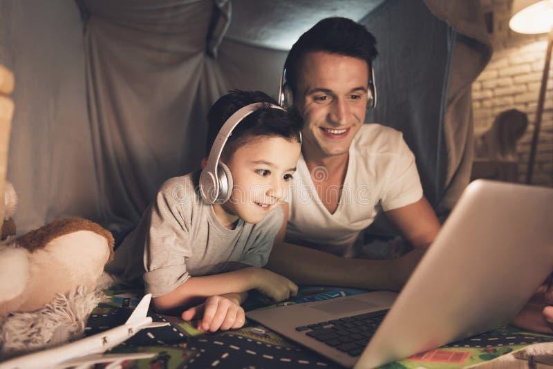 Отец и сын говорят на skype к семье на компьтер-книжке на ноче дома стоковое фото rf