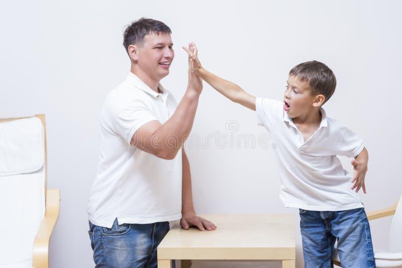 Отец и сын дают высокие 5 друг к другу стоковое фото