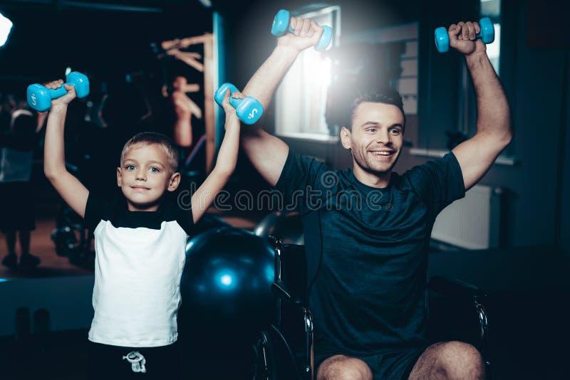 Отец и сын делают тренировки с Dumbbels стоковое фото