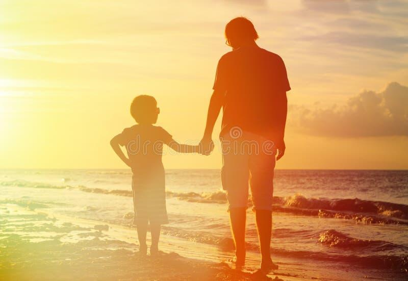 Отец и сын держа руки на заходе солнца стоковое изображение rf