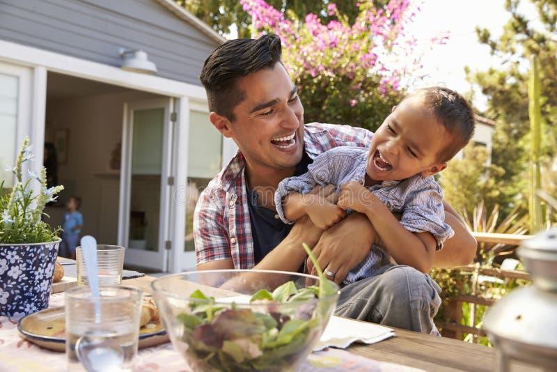 Отец и сын есть внешнюю еду в саде совместно стоковая фотография rf