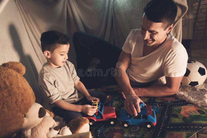 Отец и сын играют с автомобилями игрушки на дороге ковра на ноче дома стоковые фотографии rf