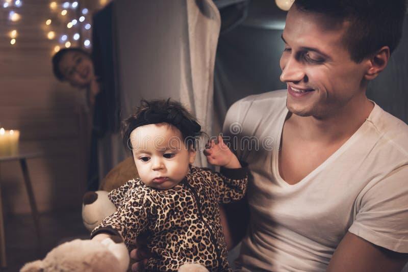 Отец и сын играют с маленькой сестрой младенца на ноче дома стоковые изображения rf