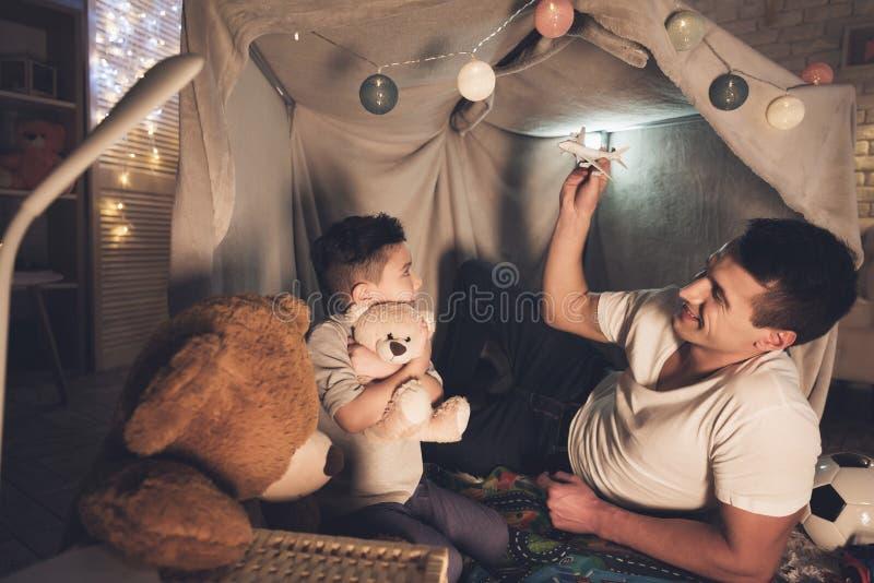 Отец и сын играют с самолетом и автомобилями игрушки на ноче дома стоковые фотографии rf