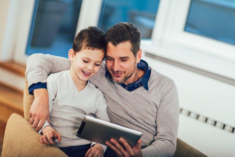 Отец и сын играя на планшете дома, имеющ потеху стоковое фото rf