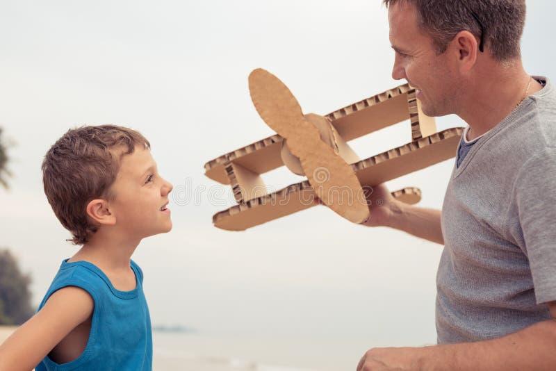 Отец и сын играя с самолетом игрушки картона стоковая фотография rf