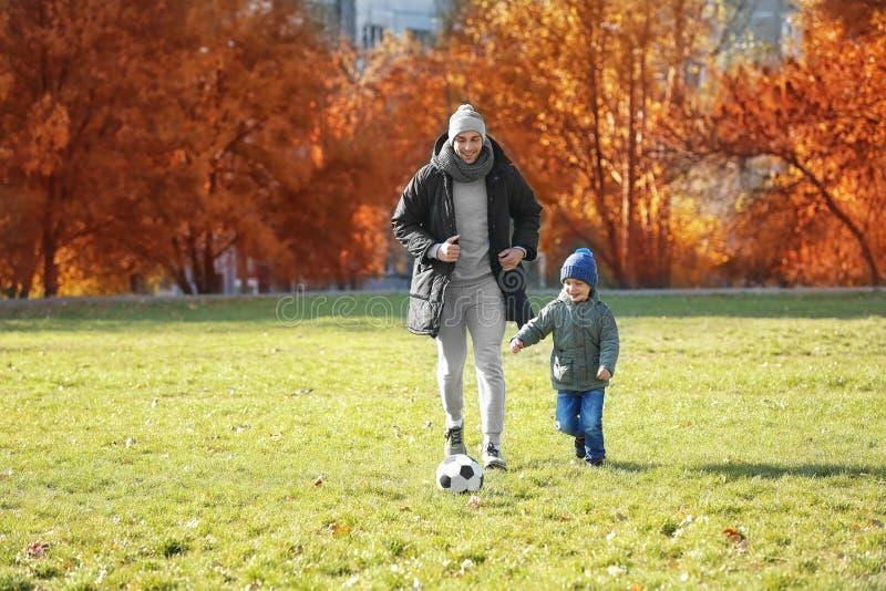 Отец и сын играя футбол на тангаже стоковые изображения