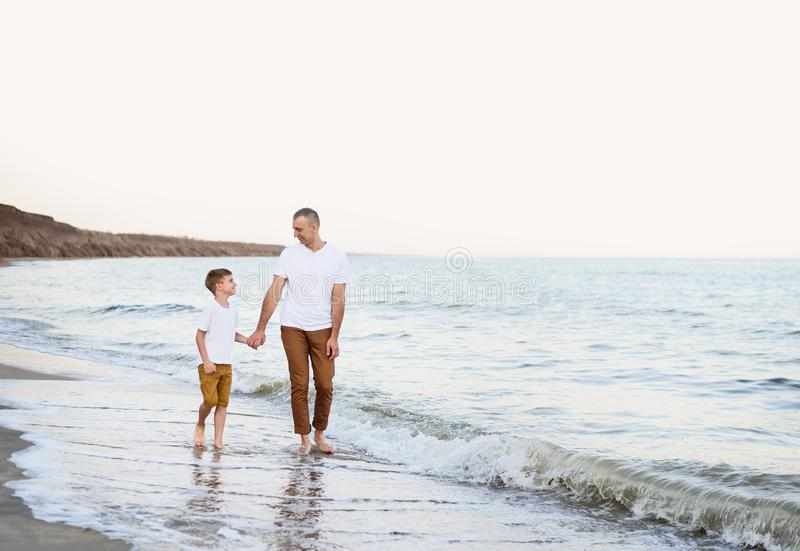 Отец и сын идут рукой вдоль семейного отдыха морского побережья r стоковые изображения