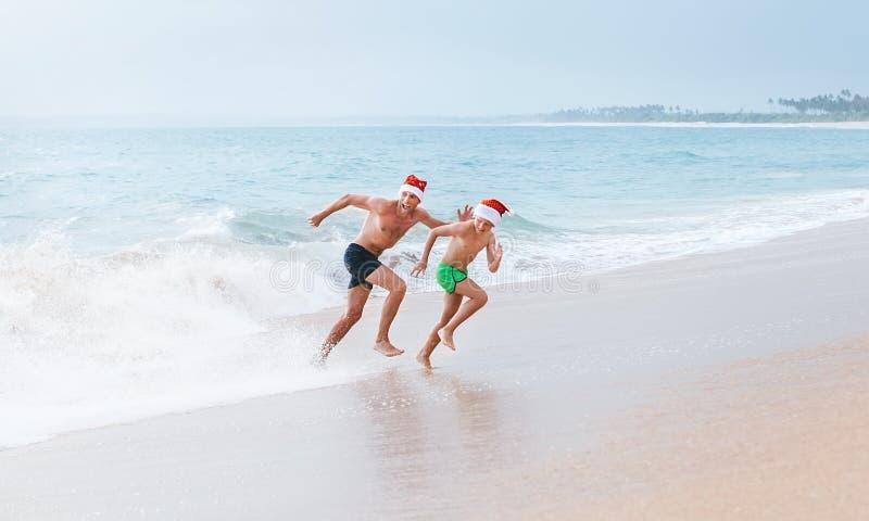 Отец и сын имеют потеху на пляже океана, бегут далеко от большой волны стоковые фотографии rf