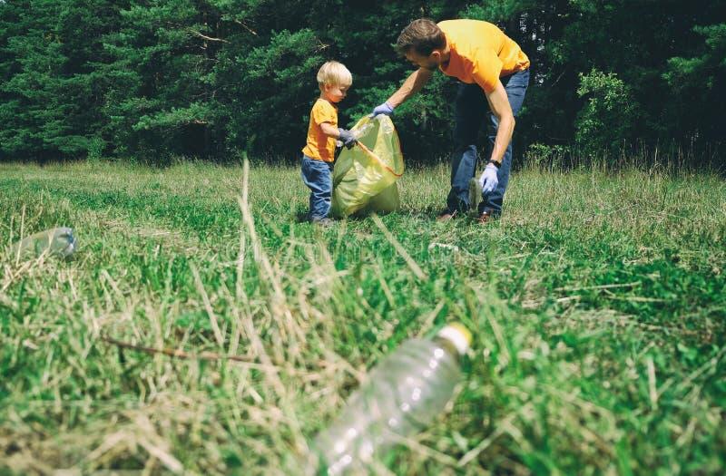 Отец и сын комплектуя вверх пластиковый отброс для очищая парка Волонтеры tidying вверх по хламу в концепции леса экологического стоковые фотографии rf
