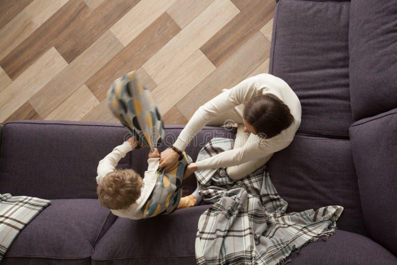 Отец и сын наслаждаясь боем подушками на софе, взгляд сверху стоковая фотография