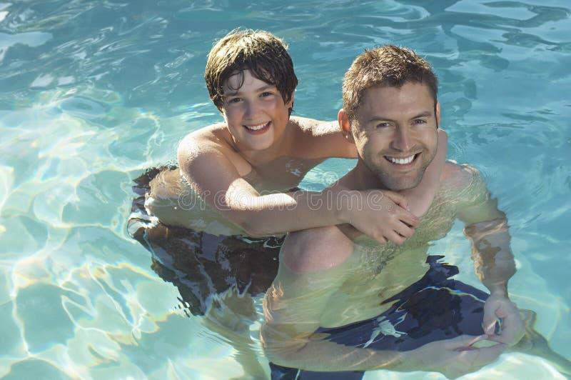 Отец и сын наслаждаясь в бассейне стоковое изображение