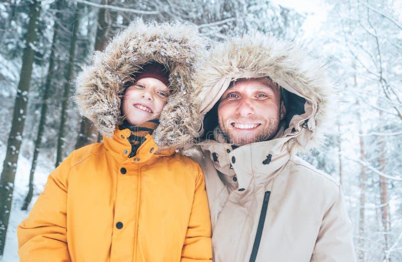 Отец и сын одетые в теплом с капюшоном случайном Outerwear куртки Parka идя в портрет сторон снежного леса жизнерадостный усмехая стоковая фотография rf