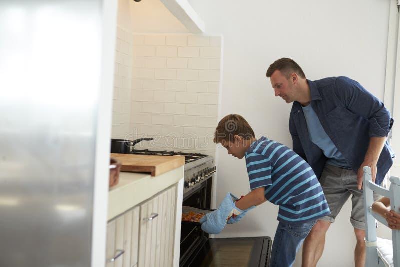 Отец и сын печь домодельную пиццу в печи стоковое изображение rf