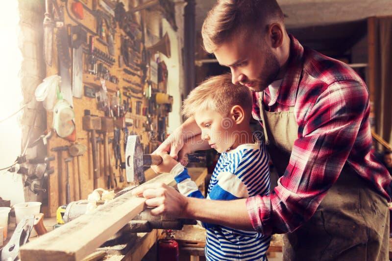 Отец и сын при молоток работая на мастерской стоковая фотография rf